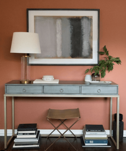 Light blue Console table with lamp and plant on top in front of an accent wall
