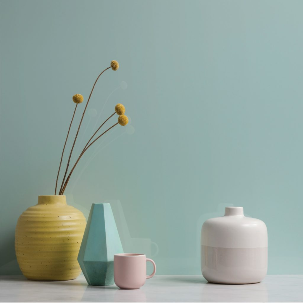 Close up of three vases and a mug in pastel shades on a glossy aquamarine wall panel
