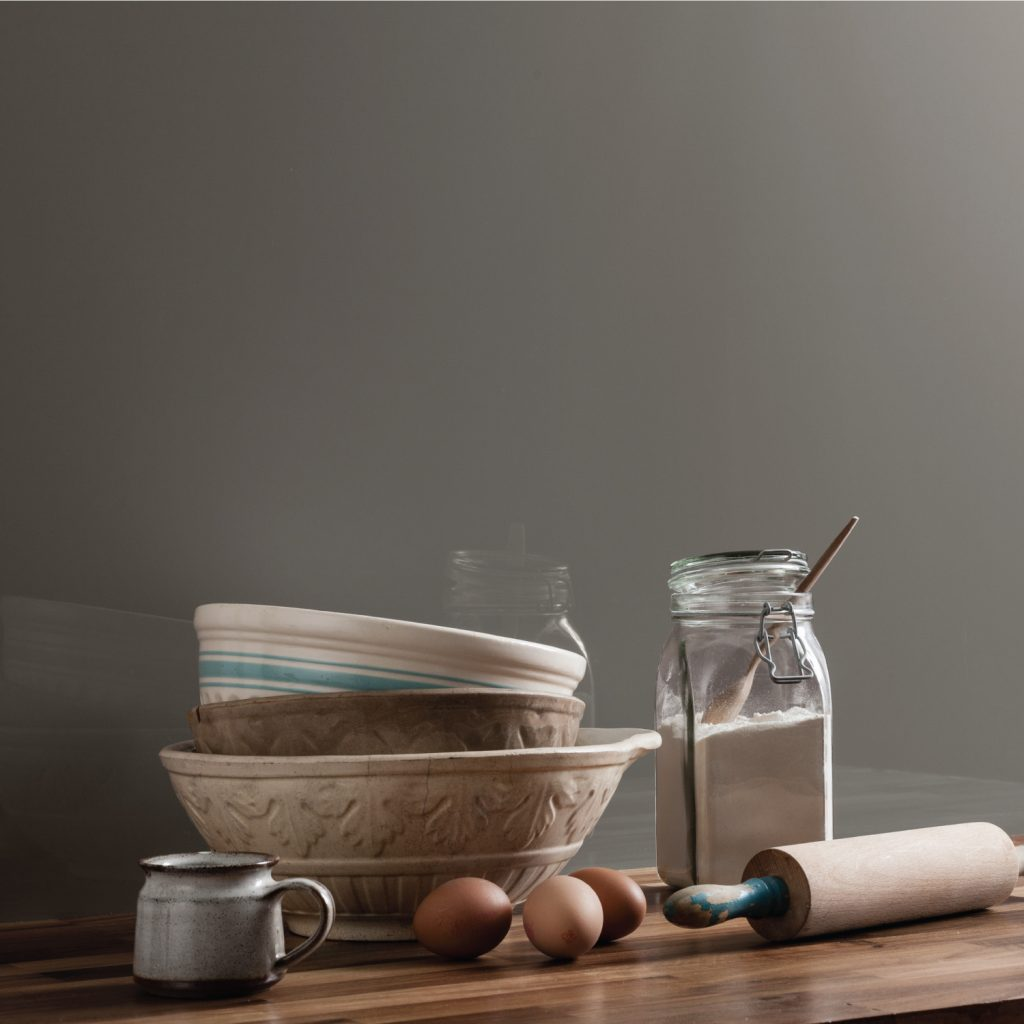 Close up of a kitchen featuring a warm grey kitchen wall panel with a chopping board, a tea pot and a cauliflower