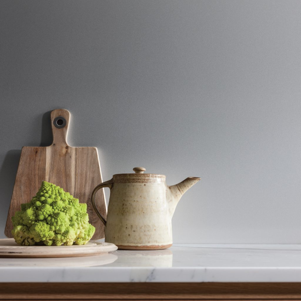 Close up of a kitchen featuring a light grey AluSplash wall panel with a chopping board, a tea pot and a cauliflower