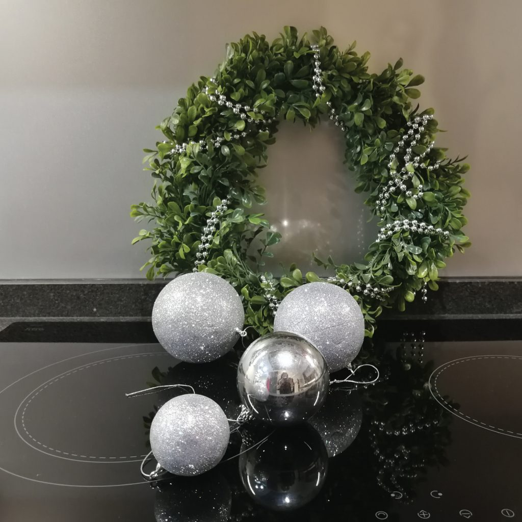 Silver Christmas balls and wreath placed on a cooktop with grey backslash behind