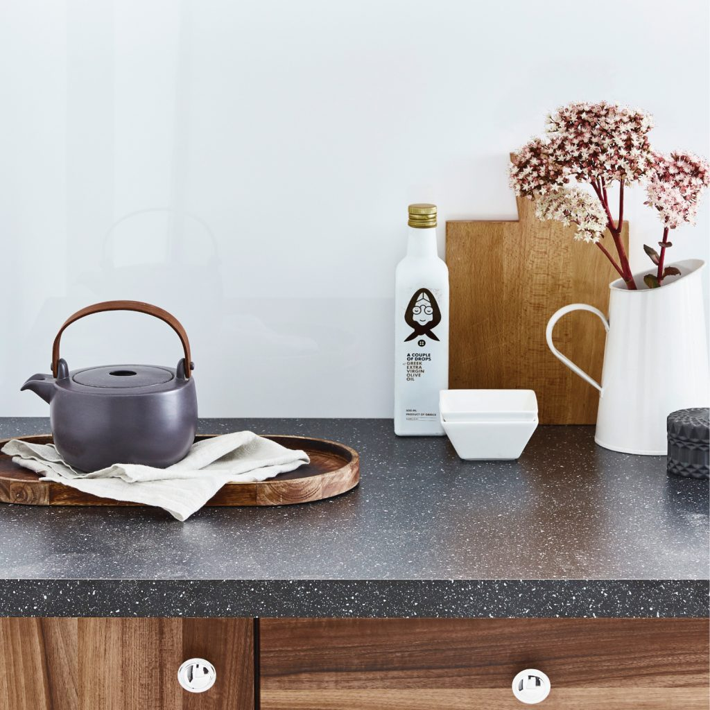 White kitchen splashback featuring zen-like white and wooden ornaments on a black granite countertop