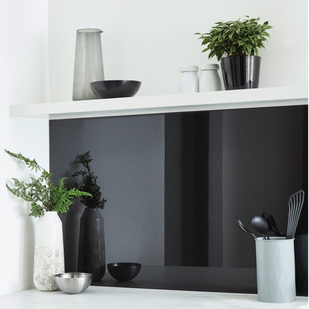 Black glass looking splashback in a white kitchen with kitchen tools
