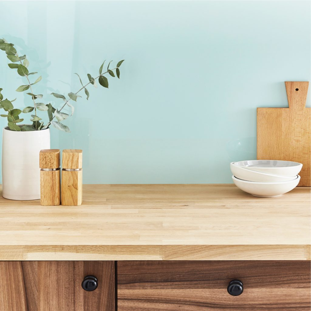 Glossy light blue kitchen splashback installed over a wooden cabinet and countertop featuring wooden and white kitchen tools