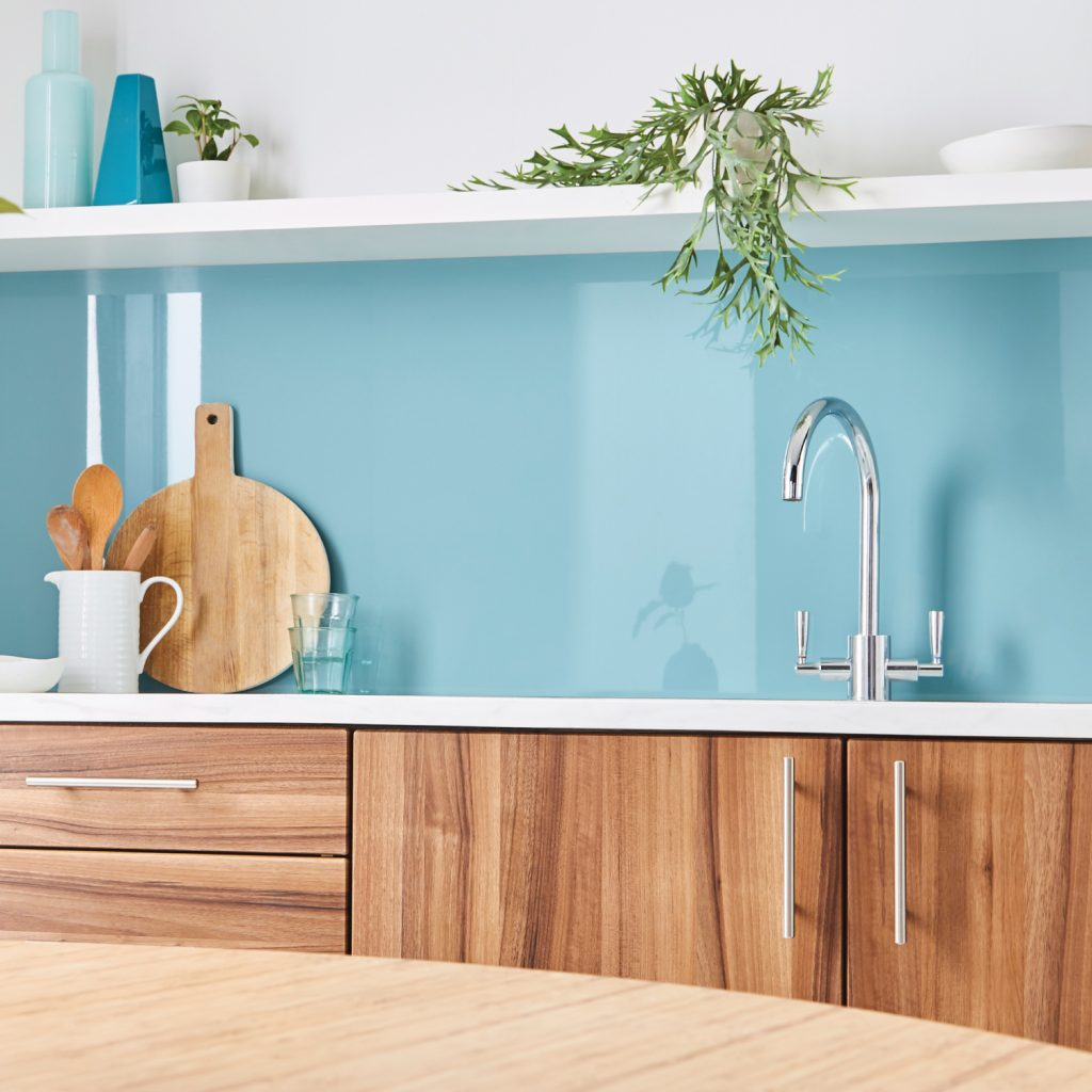 Glossy light blue kitchen splashback featuring wooden chopping board and spoons and a plant