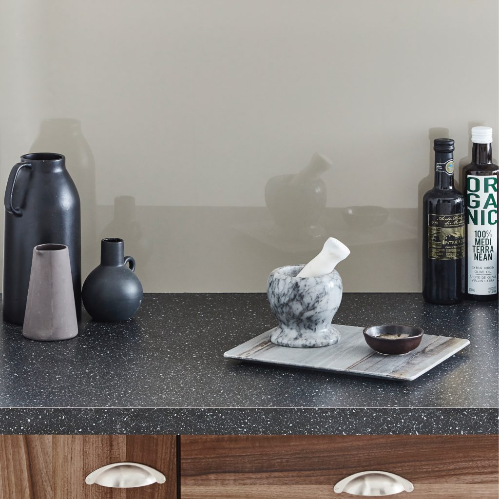 Glossy warm gray splashback featuring dark granite countertop,marble tools and bottles of oil