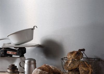 Modern industrial kitchen with a silver brushed Alusplash splashback and a wooden countertop with bread in baskets and bowls