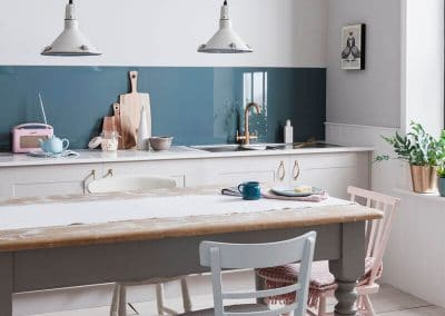Rustic kitchen with a Petro Blue Alusplash splashback and cheese cake in a plate on a wooden dining table herbs
