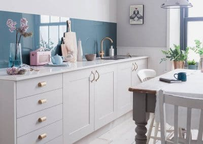 Rustic kitchen with a Petrol Blue Alusplash splashback and cheese cake in a plate on a wooden dining table with kitchen accessories