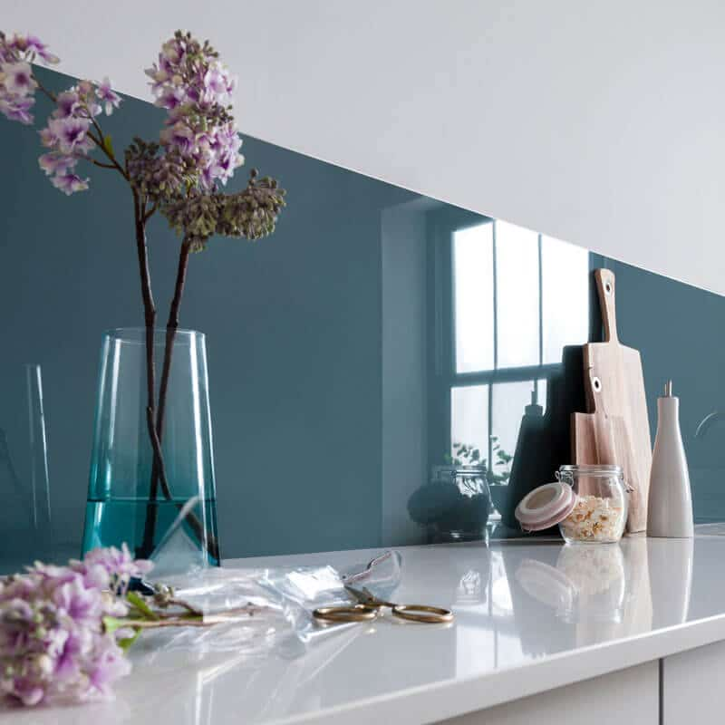 Rustic kitchen with a Petrol Blue Alusplash splashback and white countertop and purple flowers with glass pot