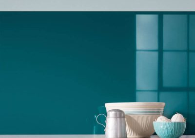 Glass-like splashback in a blue colour, Totally Teal from the Elegance Collection of Alusplash paired with a marble countertop with Eggs in pot and milk glass bottle