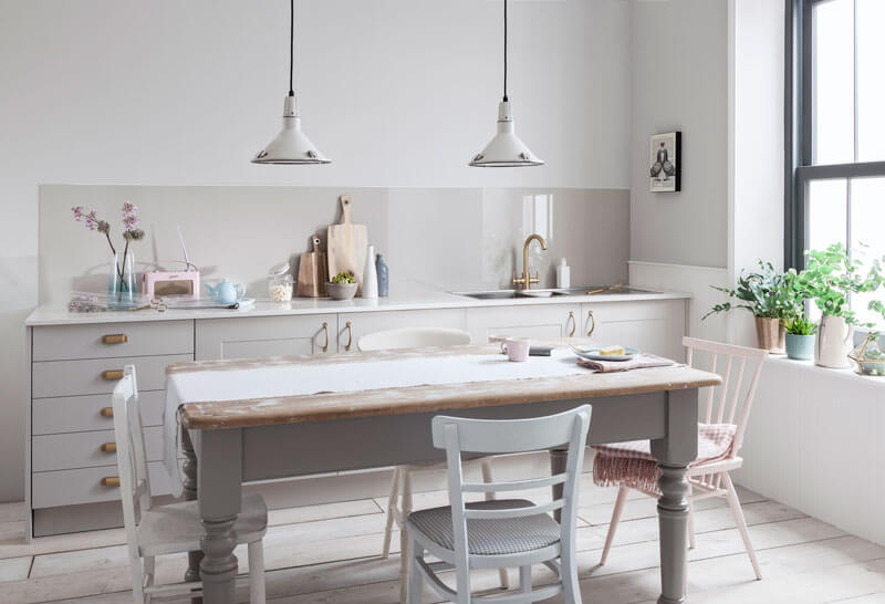 Rustic kitchen with a Warm Grey Alusplash splashback and cheese cake in a plate on a wooden dining table with kitchen accessories