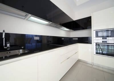 White modern kitchen with a Stardust Black Alusplash splashback in high gloss.