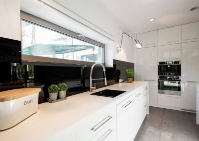 White modern kitchen with a Stardust Black Alusplash splashback and white countertop with potted herbs on top