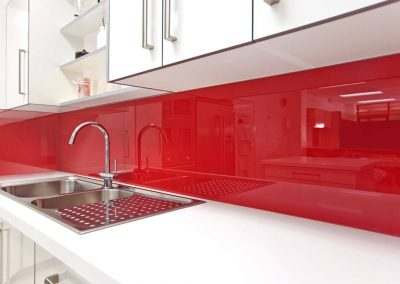 White kitchen cabinets with a spanish red Alusplash splashback and white countertop