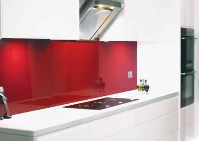 White kitchen cabinets with a spanish red Alusplash splashback and white countertop and edible oil bottles