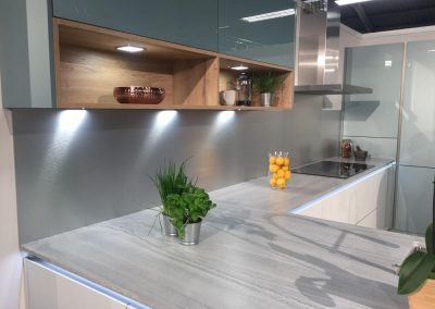 kitchen with a silver brushed Alusplash splashback and grey marble countertop with lemons in glass jug