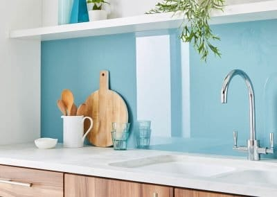 Modern kitchen with a high gloss Alusplash splashback in blue bird and white countertop with wooden kitchen tools