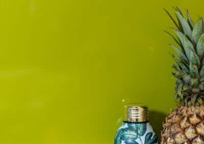 Olive Green Kitchen Alusplash splashback with a white marble textured countertop and pineapple with bottle