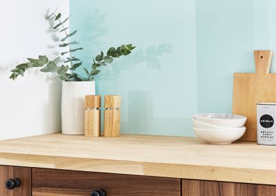 Wooden kitchen cabinets with an ocean wave Alusplash splashback and wooden countertop with green plant
