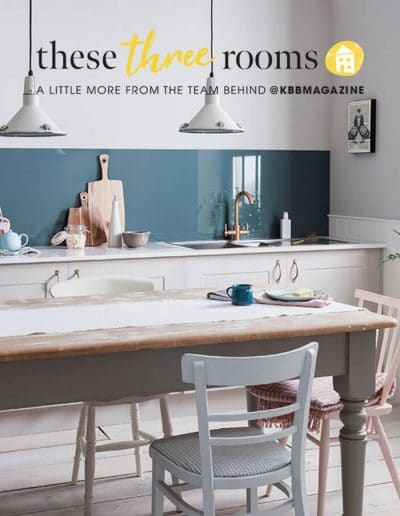 Alusplash splashbacks featured on These three rooms KBB magazine. Magazine cover showing kitchen in petrol blue Alusplash splashback with a glossy white marble countertop and wooden dining table