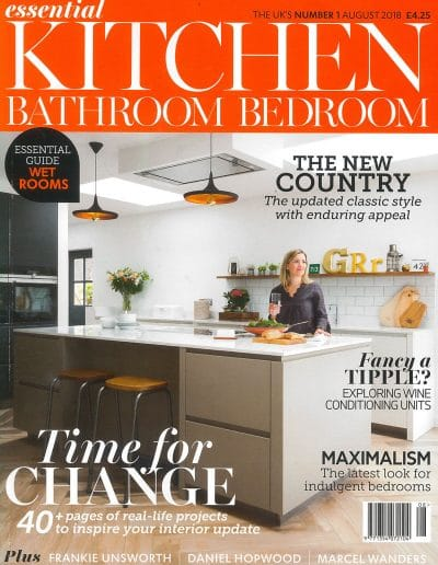 Alusplash splashbacks featured on Essential Kitchen Bathroom Bedroom magazine. Magazine cover showing latest classic style for moden kitchen with splashback and countertop, Lady sitting on dining table