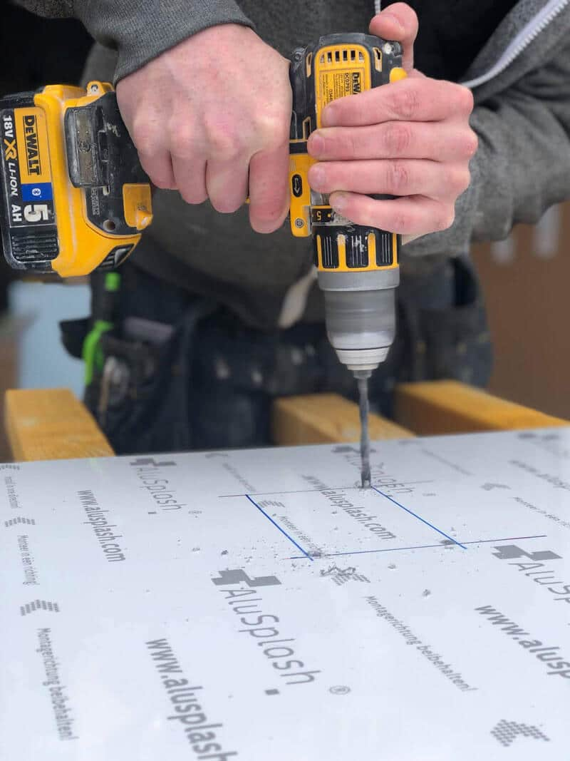 How to fit Alusplash: Installer working on an blue AluSplash panel with a drill to make cut our for sockets