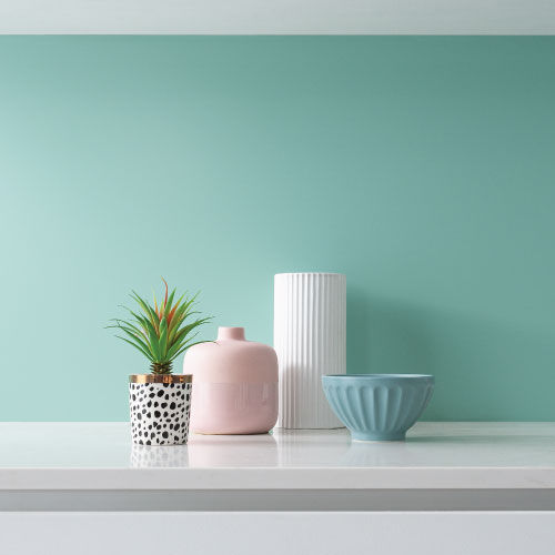 Coloured kitchen with a light green splashback and pastel shade kitchen accessories