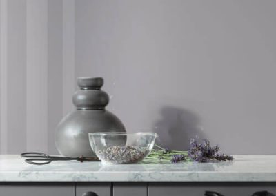 Modern kitchen with a high gloss splashback in a Grey Lavender colour, matt grey cabinets, Glass bowl holds Lavender flowers with scissor and metal pot
