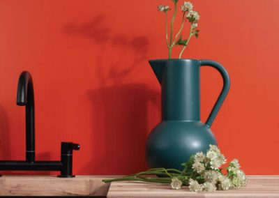 Kitchen sink, wooden countertop and a matte orange splashback in an Autumn Leaves variation from the Elements Collection with a jar and flowers