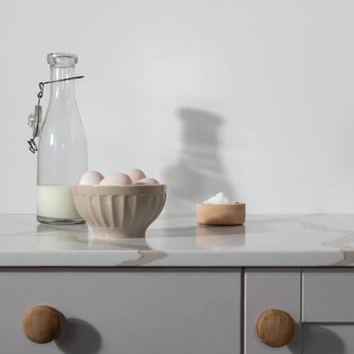 Country style kitchen with a matt iceberg white Alusplash splashback from the Elments Collectiion and white carrara marble countertop with Eggs in pot and milk glass bottle