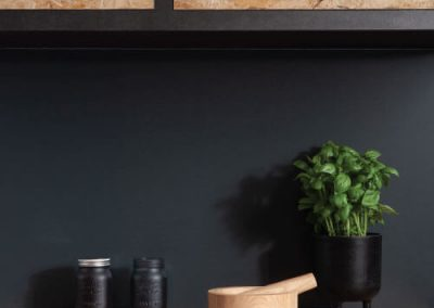 Wooden kitchen cabinets with a matt lava stone splashback from the Alusplash's Elements Collection, wooden countertop with green plant and glass jars