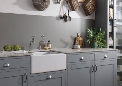 Rustic kitchen with a matt grey splashback in a Smoked Ember colour from the Alusplash's Elements Collection. Baskets hanged on wooden frame with green plants and kitchen accessories