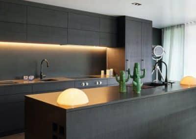 Contemporary kitchen with a matt lava stone Alusplash splashback and dark countertop and cabinets