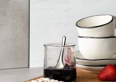 Kitchen with marble looking splashback in White Carrara from the Alusplash collection with detail of black anthracite edge profile. Wooden board with cracker, jam and coffee cups piled up in the foreground