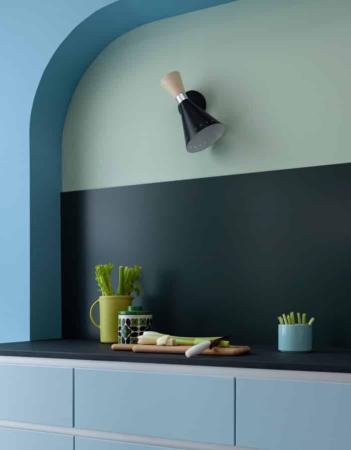 Matt green Alusplash kitchen backsplash in a futuristic kitchen with blue cabinets